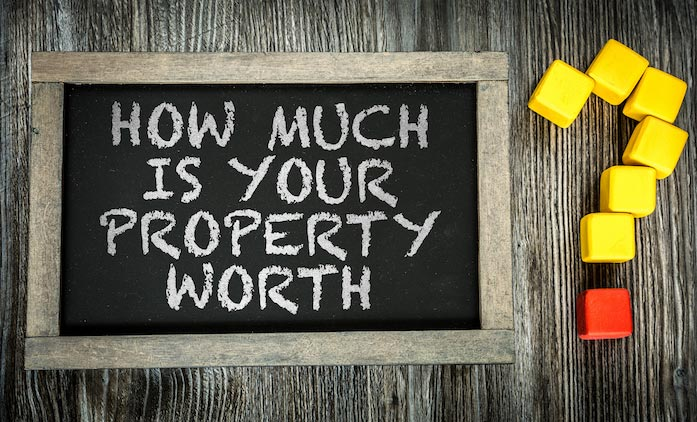 Blackboard with the text: How much is your property worth? on it